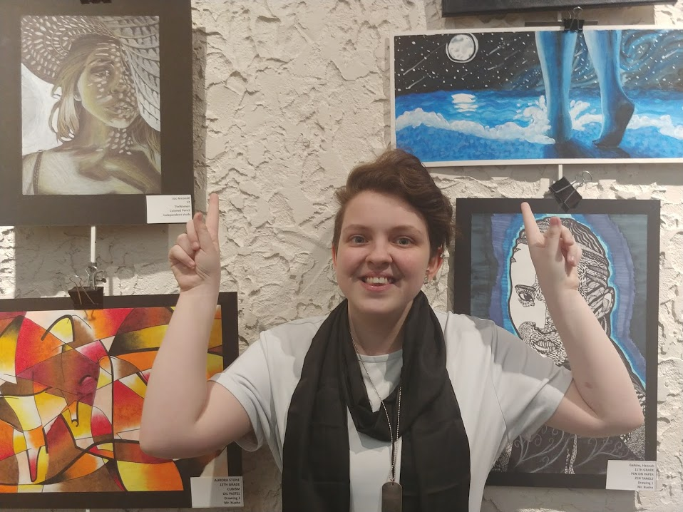 Joc Arconati, pointing at two of their art pieces
